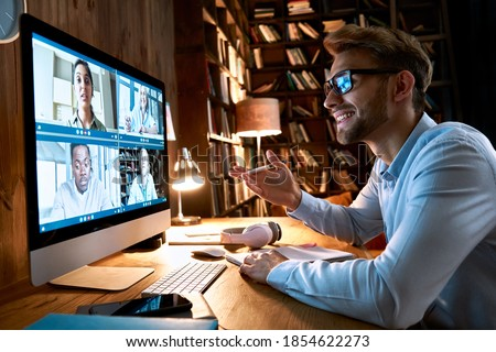 Business man having virtual team meeting on video conference call using computer. Social distance worker working from home office talking to diverse colleagues in remote videoconference online chat. Royalty-Free Stock Photo #1854622273