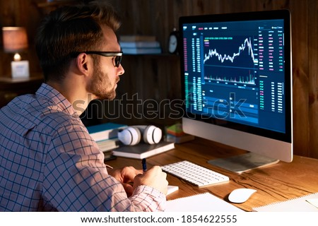 Serious business man trader analyst looking at computer monitor, investor broker analyzing indexes, financial chart trading online investment data on cryptocurrency stock market graph on pc screen. Royalty-Free Stock Photo #1854622555