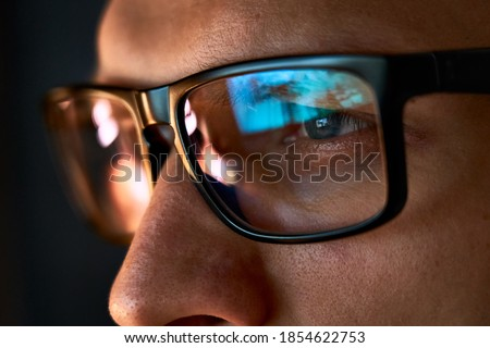 Close up view of focused businessman wears computer glasses for reducing eye strain blurred vision looking at pc screen with computer reflection using internet, reading, watching, working online late. Royalty-Free Stock Photo #1854622753