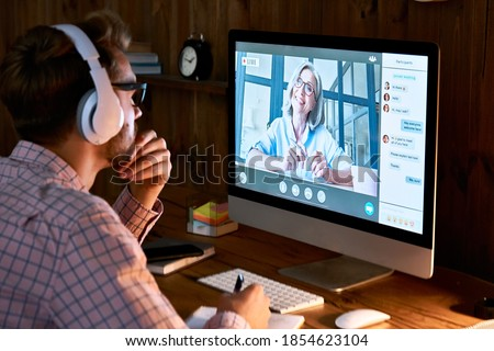 Male student wearing headphones taking online course training, watching webinar, remote seminar university class, virtual learning with social distance web teacher, tutor or coach on computer screen. Royalty-Free Stock Photo #1854623104