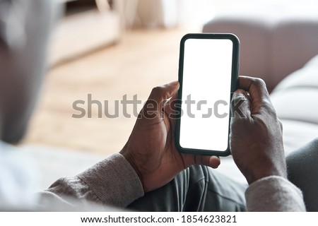 African american man holding smart phone with mockup white blank display, empty screen for app ads sitting on couch at home. Mobile applications technology concept, over shoulder close up view. Royalty-Free Stock Photo #1854623821