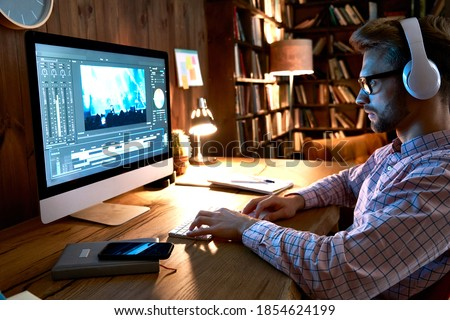 Videographer editor film maker wears headphones using digital software on desktop computer editing video footage visual content working at home office using post production multimedia making montage. Royalty-Free Stock Photo #1854624199