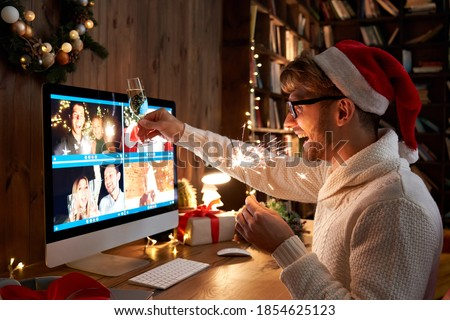 Young man wearing Christmas hat drinking champagne holding sparkler talking to friends on virtual zoom video call celebrate Happy New Year party in distance online conference chat on computer at home. Royalty-Free Stock Photo #1854625123