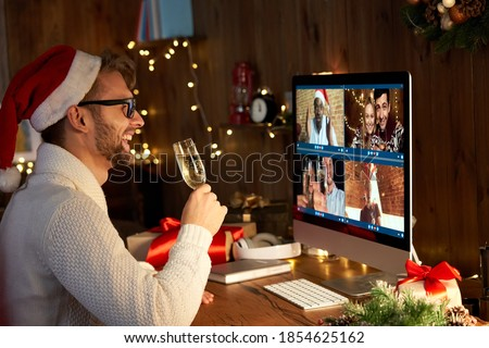 Happy young man wears santa hat drinking champagne talking meeting friends on virtual zoom video call celebrate New Year party in holiday distance online conference chat together on computer at home. #1854625162