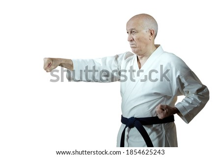 On white isolated background old man athlete in karategi beats hand punch Royalty-Free Stock Photo #1854625243