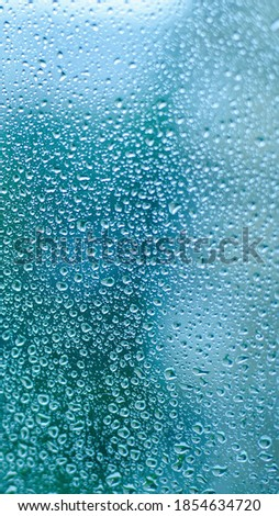 Drops of rain on window glass. Shallow DOF. Natural Blue Water background with Raindrops for sad mood and thoughts. Selective focus