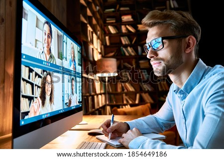 Business man having virtual team meeting on video conference call using computer. Social distance employee working from home office talking to diverse colleagues in remote videoconference online chat. Royalty-Free Stock Photo #1854649186