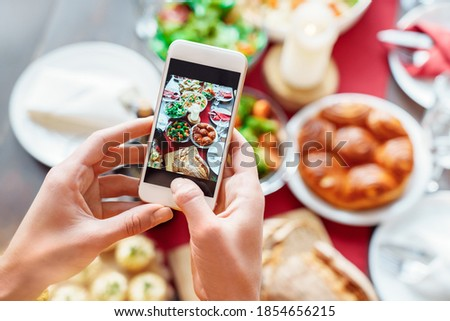 Female hands making photo of healthy vegetarian family holiday dinner setting on smartphone. Christmas, New year, Thanksgiving, Anniversary, Hanukkah, Mothers day, food photo and delivery concept