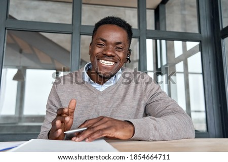 Cheerful african business man talking to web cam on conference call. Happy black businessman, coach, tutor wearing headset laughing, looking camera during webinar, online class, webcam view. Headshot #1854664711