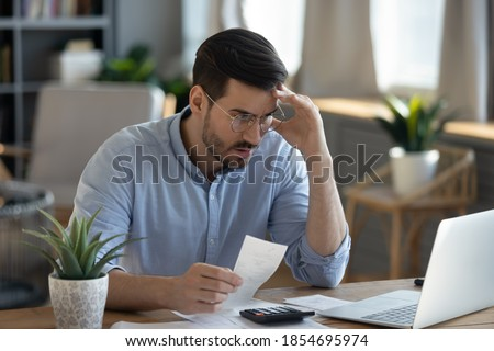 Small business owner experiences financial crisis, high costs, bank debt, money overspend concept. Man sitting at desk looks at laptop screen holding receipt feels desperate after calculating expenses Royalty-Free Stock Photo #1854695974