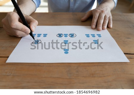Businessman sit at table working on project strategy, close up view male hands holding felt pen creates multi-level network marketing scheme on paper. Visual plan, advertising, pyramid selling concept