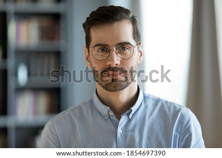Head shot young attractive businessman in glasses standing in modern office pose for camera. Videoconference call profile picture handsome entrepreneur portrait, professional occupation person concept