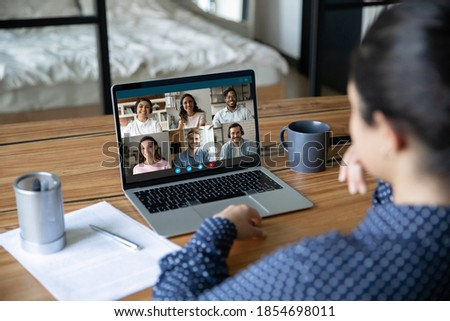 Rear view young indian ethnicity employee holding video conference web cam online meeting with happy mixed race colleagues, discussing working issues distantly at home office using computer app. Royalty-Free Stock Photo #1854698011
