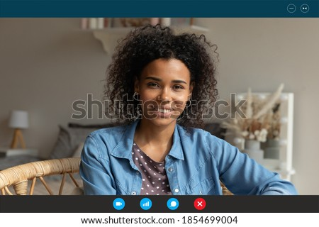 Head shot relaxed young african american attractive happy woman looking at web camera, enjoying nice pleasant weekend leisure remote talk with friends, using video call computer application at home. Royalty-Free Stock Photo #1854699004