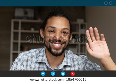 Close up happy young handsome african ethnicity man employee waving hand, welcoming colleagues teammates at online distant meeting, using computer software video call application, working from home. Royalty-Free Stock Photo #1854700012