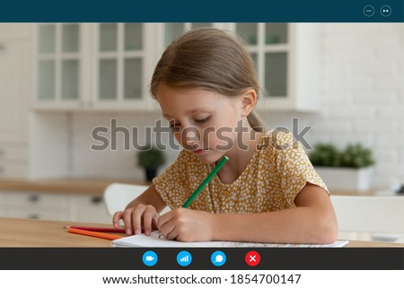 Computer video call application screen view focused little adorable 7s girl drawing pictures at home or studying at online distant creative class, sitting at table indoors, distant communication