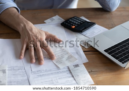 Individual entrepreneur make analysis of firm expenses, accountant do paperwork concept. On desk lot of receipts, calculator and laptop close up view. Man sit at table reviewing bills, managing budget Royalty-Free Stock Photo #1854710590