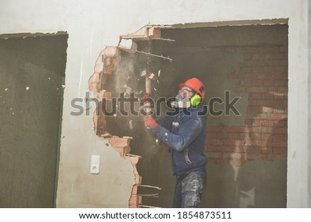 demolition work and rearrangement. worker with sledgehammer destroying wall Royalty-Free Stock Photo #1854873511