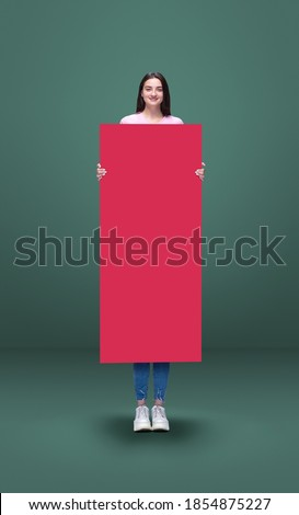 Tall high woman and long banner isolated on green studio background. Unusual delighted and long. Copyspace for offer, advertising, artwork, inspiration and hobby, mood concept. Humor, weird collage. Royalty-Free Stock Photo #1854875227