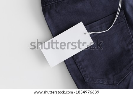 White clothing tag mockup on a blue pants.