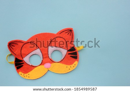 Cat Carnaval mask on blue background. Top view, copy space