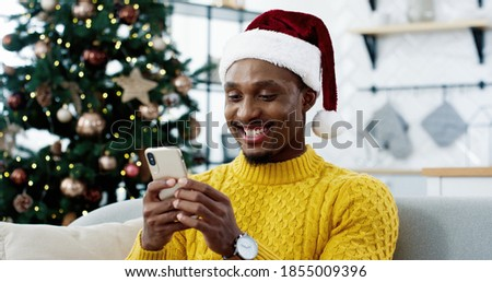 African American joyful surprised man on Christmas Eve receive great news on cellphone about lottery win auction victory feeling happy. Unbelievable luck, New Year miracle, candid emotions, Xmas sale #1855009396