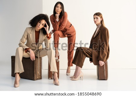 full length of stylish multicultural women in suits sitting on suitcases on white Royalty-Free Stock Photo #1855048690