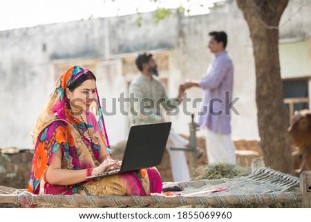 Indian Women using laptop at village Royalty-Free Stock Photo #1855069960