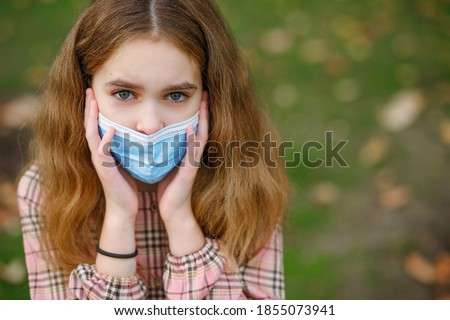 COVID-19 Coronavirus pandemic girl child in a city park wearing a mask protecting against the spread of the SARS-CoV-2 virus. Girl with a surgical mask on her face against coronavirus disease Royalty-Free Stock Photo #1855073941