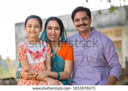 Indian family sitting on traditional bed in village Royalty-Free Stock Photo #1855078675