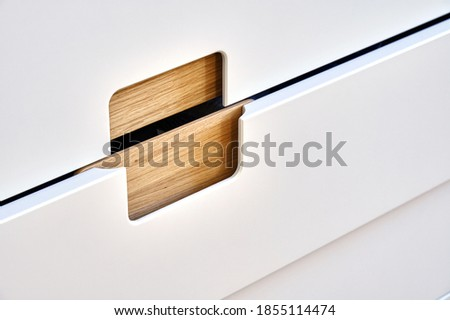 Detail of the wardrobe close-up. Modern wooden wardrobe with flat finger pull wardrobe doors. Oak veneered plywood cabinets with light gray painted cabinet doors. Modern furniture Royalty-Free Stock Photo #1855114474