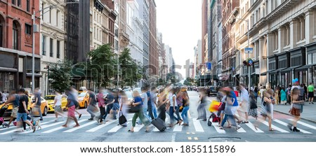 Busy street scene in New York City with groups of people walking across a crowded intersection on Fifth Avenue in Midtown Manhattan NYC Royalty-Free Stock Photo #1855115896