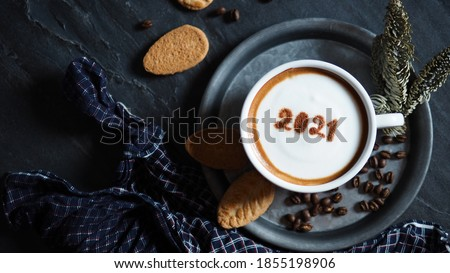 Welcome 2021 holidays food art theme coffee cup with number 2021 over frothy surface served on aluminum plate with biscuits, coffee beans and dried pine branches on black stone background with napkin.