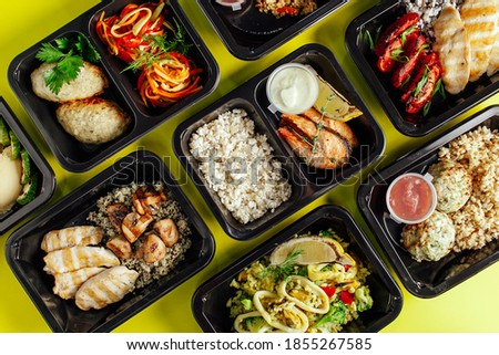 Healthy lunch at the workplace. Pick up food in black containers with Cutlery on a yellow background Royalty-Free Stock Photo #1855267585