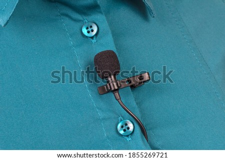Audio recording of sound on a condenser microphone. The lavalier microphone is secured with a clip on a woman's shirt close-up.