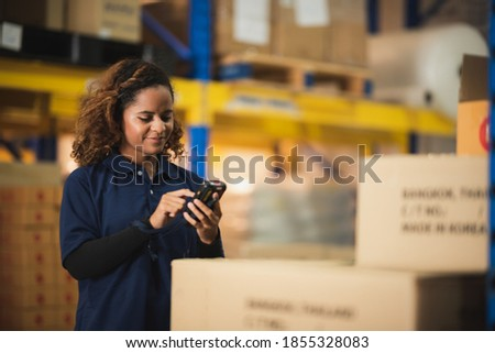 warehouse worker using bar code scanner to analyze newly arrived goods for further placement in storage department, logistic working at warehouse. Royalty-Free Stock Photo #1855328083