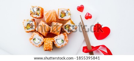 Banner. Valentine's Day. Sushi and sticks on a white background. The concept of a romantic dinner at a sushi bar. The portfolio has more images by February 14th. Royalty-Free Stock Photo #1855395841