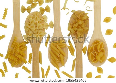 five different types of pasta lie on a white plate in spoons