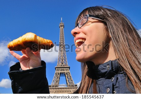 Woman eating a croissant in front of the Eiffel Tower. Royalty-Free Stock Photo #185545637