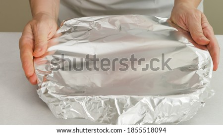 Chef wraps baking pan with aluminum foil. Baking process Royalty-Free Stock Photo #1855518094