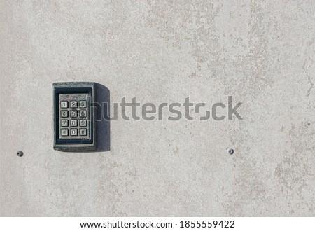 numeric keypad on concrete wall Royalty-Free Stock Photo #1855559422