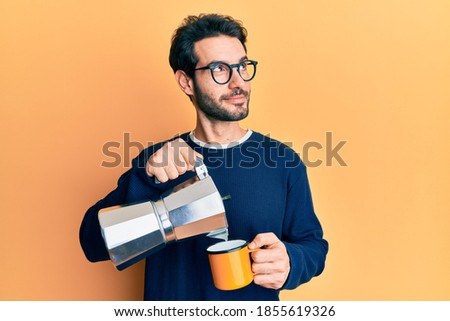 Young hispanic man drinking italian coffee smiling looking to the side and staring away thinking.  Royalty-Free Stock Photo #1855619326
