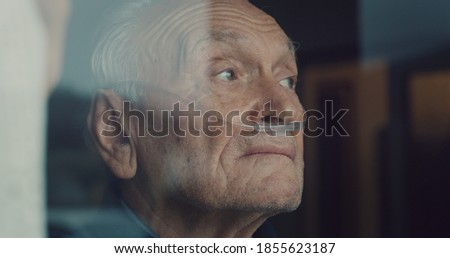 Cinematic close up shot of an elderly thoughtful man wearing oxygen tube is looking through a window in the morning. Concept of healthcare, life, pensioner, grandparents, retirement, boarding house. Royalty-Free Stock Photo #1855623187