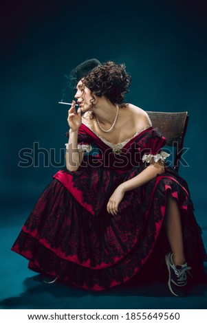 Cigarette smoking. Young woman as Anna Karenina isolated on dark blue background. Retro style, comparison of eras concept. Beautiful female model like literature character, great, old-fashioned. Royalty-Free Stock Photo #1855649560