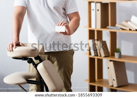 Cropped view of masseur standing near massage chair and holding blank business card in office on blurred background