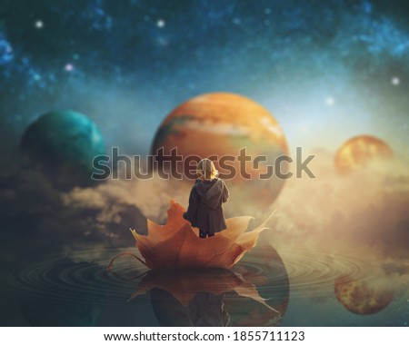 Little girl travelling through dream world, floating on a big fallen leaf; imaginationfantasy background; Elements of this image furnished by NASA Royalty-Free Stock Photo #1855711123