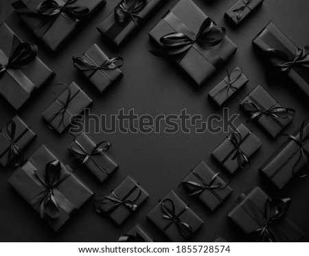 Arranged Gifts boxes wrapped in black paper with black ribbon on black background. Christmas concept #1855728574