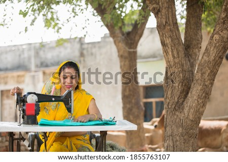 Woman sewing clothes with sewing machine Royalty-Free Stock Photo #1855763107