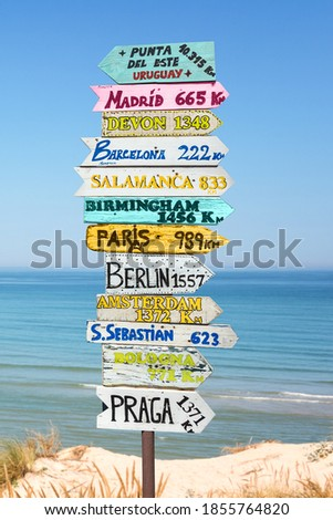 Colorful directions signs on the beach to different places of the world. Travel concept. Royalty-Free Stock Photo #1855764820