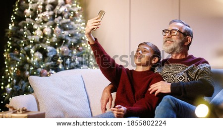 Portrait of happy smiling Caucasian old grandpa with teen grandchild sitting in decorated room and taking selfie photos on smartphone at home near glowing new year tree. Christmas holidays concept